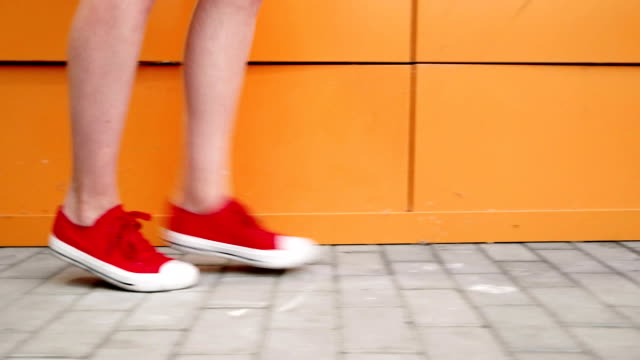 Female feet in sneakers gumshoes walking along orange wall, close up. Woman's feet in red sports shoes walking along the camera. FullHD