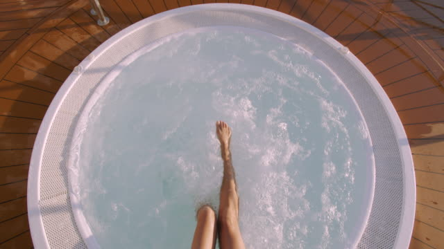 Female feet in the jacuzzi water, slowmotion video