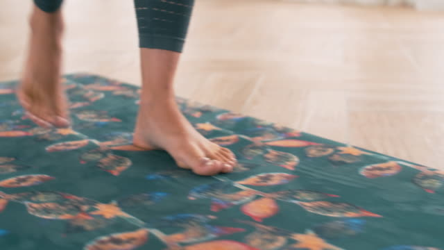 Female feet moving from toes to heels on yoga mat All-round shot of girl stepping on yoga mat and standing on toes, then on heel mindfulness stock videos & royalty-free footage