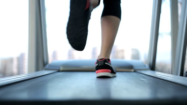 Female feet running fast on treadmill, working hard to succeed video