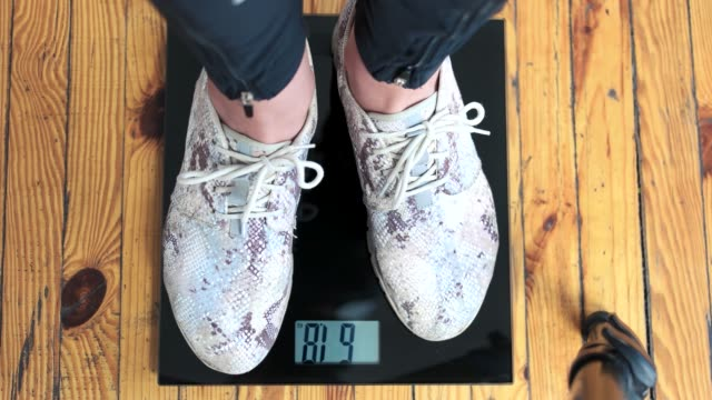 Female feet standing on weight scales.