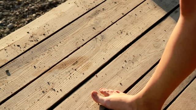 weibliche Füße zu Fuß auf einem Holzsteg am Strand – Video