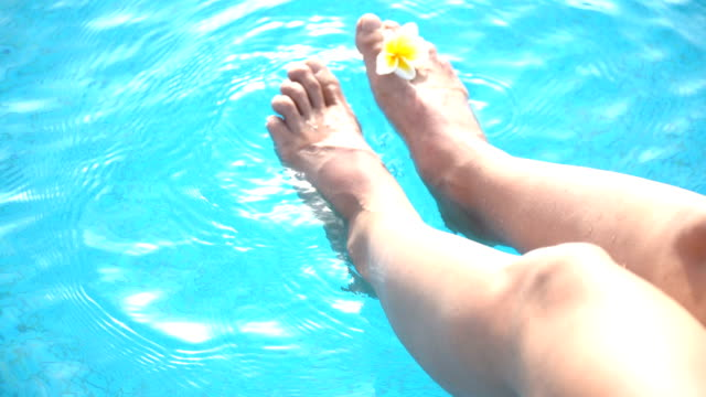 Female feet with a plumeria flower in the swimming pool blue water video
