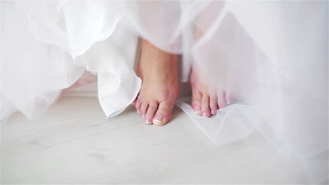 Female feet with neat polished pedicured toe nails close up. No face woman sit or stand barefoot at floor detail. Hem of dress or skirt shallow dof video
