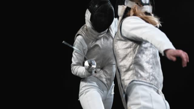 El esgrimista SLO MO hembra golpea a su oponente con la punta de la lámina - vídeo