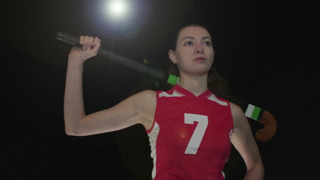 Female Field Hockey Player Portrait pose - Super Slow Motion 180 degree rotation Stock HD video clip footage of a female Field Hockey Player. Filmed in Super Slow motion, the camera rotates 180 degrees around the player. Black Background. Indoors pre game stock videos & royalty-free footage