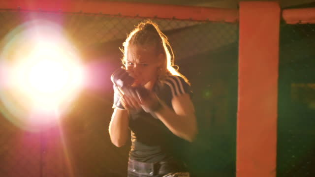 vídeos de stock e filmes b-roll de a female fighter in protective gloves shows off her punching skills. - campeão desportivo