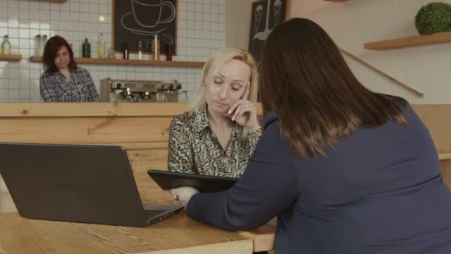 vídeos y material grabado en eventos de stock de asesor financiero femenino consultor cliente en café - planificación financiera