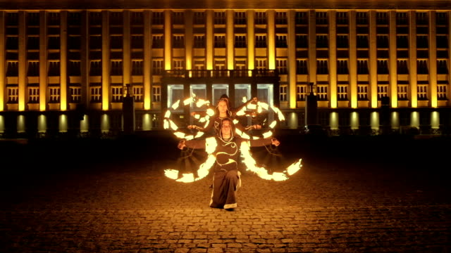 female fire show performer at night. poi performance. caucasian girl with fire acrobatics. - circus стоковые видео и кадры b-roll