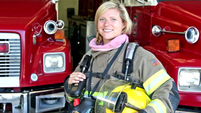 Female firefighter standing in front of fire engines video