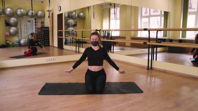 stockvideo's en b-roll-footage met vrouwelijke bus van de geschiktheidsyogatrainer die yogameditatieoefeningen op zwarte mat in lege gymnastiek voor spiegel doet die beschermend zwart masker van coronavirus covid-19 dragen - mirror mask