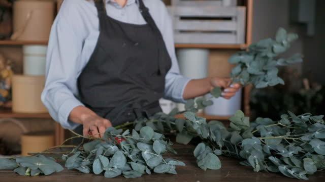 Female florist cutting eucalyptus leaves with secateurs