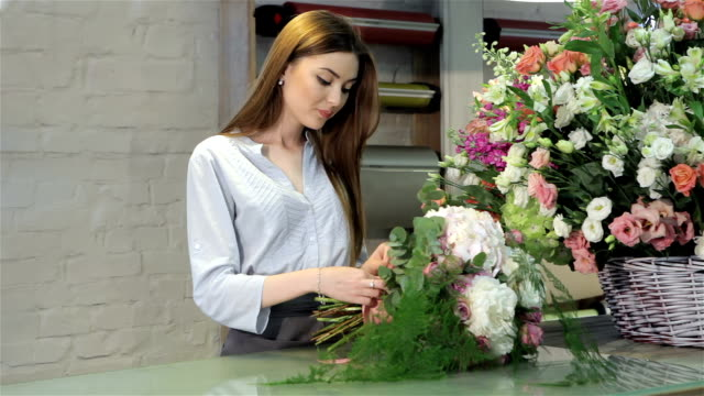 Female florist demonstrate a bouquet of white flowers at flower shop video