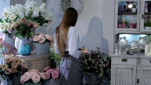Female florist inspecting flowers at her flower shop video