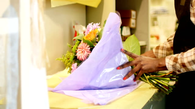 Female florist preparing flower bouquet in flower shop 4k video