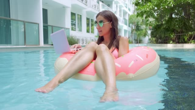 female freelancer sits in an inflatable circle in the pool and drops the laptop into the water. busy during the holidays. the concept of remote work. selective focus - служащая стоковые видео и кадры b-roll