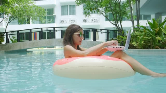 female freelancer sits in an inflatable circle in the pool and throws the laptop into the water. busy during the holidays. the concept of remote work. selective focus - служащая стоковые видео и кадры b-roll