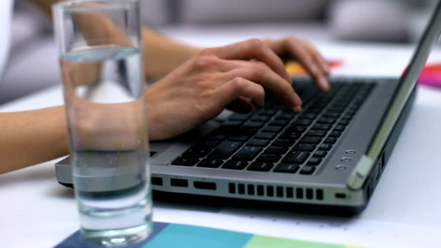 Female freelancer working laptop close-up, glass of water on table, journalist