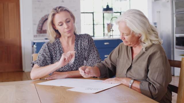 vídeos de stock, filmes e b-roll de mulher sênior de ajuda do amigo fêmea para terminar a última vontade e o testamento em casa - assistente jurídico