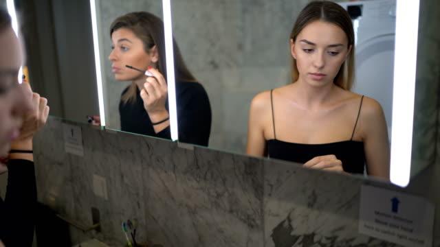 female friends applying make-up in bathroom - amicizia tra donne video stock e b–roll