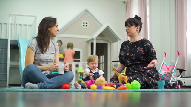 Female Friends Chatting While Their Kids Playing Female Friends Chatting and Drinking Tea While Their Kids Playing in Nursery. Slow Motion. The Concept of Childhood, Friendship, Family and Lifestyle cousin stock videos & royalty-free footage