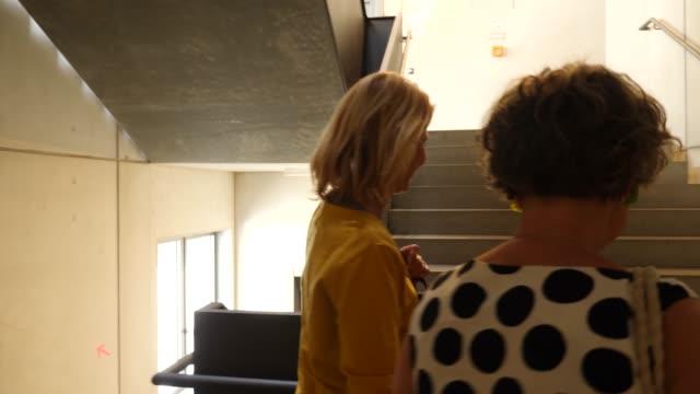 Female friends climbing stairs of dance studio