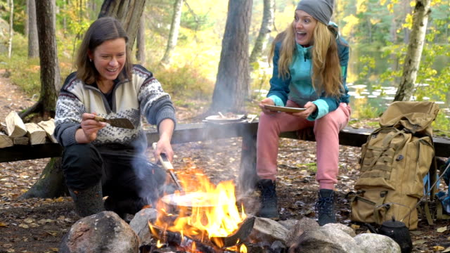 Female friends cooking traditional pancakes over an open fire in the camp outdoor during a hike