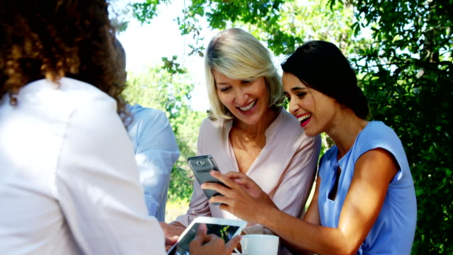 Female friends discussing over mobile phone at outdoor café video