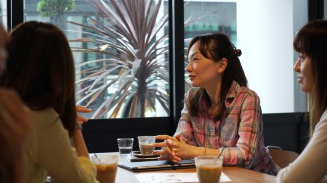 female friends enjoy talking at cafe - quarantenne video stock e b–roll