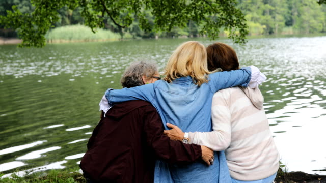 amiche che si divertono in riva al lago nella foresta - donne mature video stock e b–roll