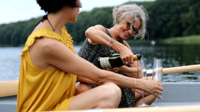 kvinnliga vänner njuta av champagne i båt - aktiva pensionärer utflykt bildbanksvideor och videomaterial från bakom kulisserna