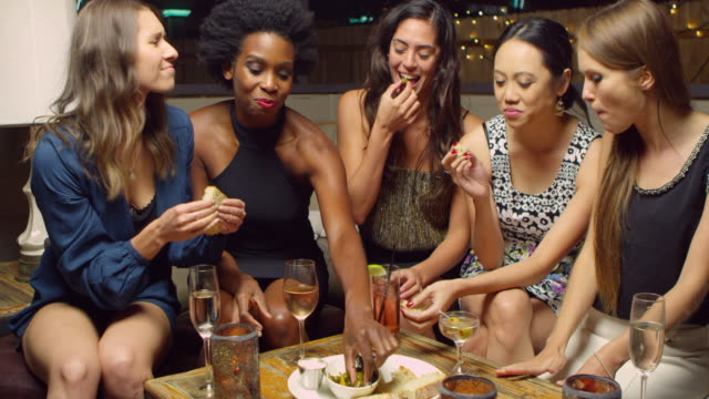 Female Friends Enjoying Night Out At Rooftop Bar Shot On R3D video