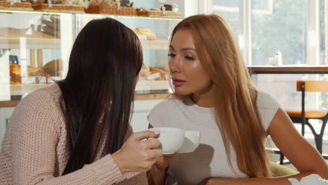 Female friends gossiping, discussing shocking news over cup of coffee
