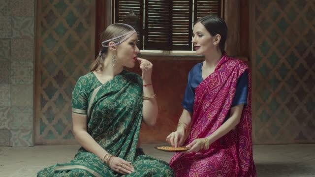 vídeos de stock e filmes b-roll de female friends in sari tasting fragant indian dish - exotismo