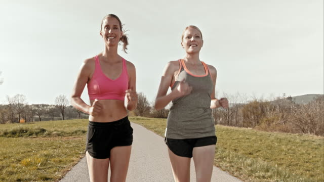 SLO MO TS Female friends jogging on a sunny day video