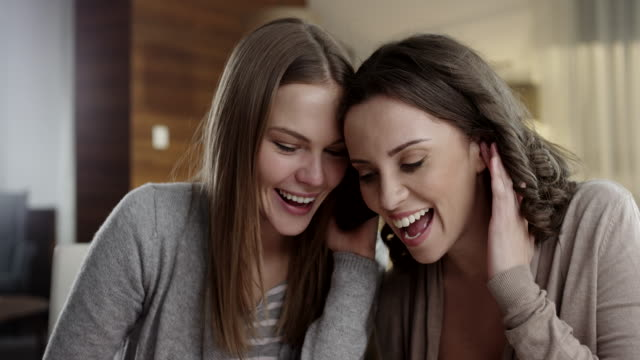Female friends listening to smartphone together