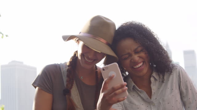 female friends look at photos on phone by manhattan skyline - friends стоковые видео и кадры b-roll