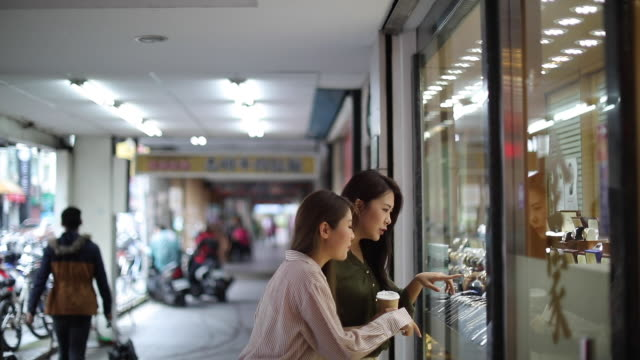 Female friends looking at window store in shopping mall