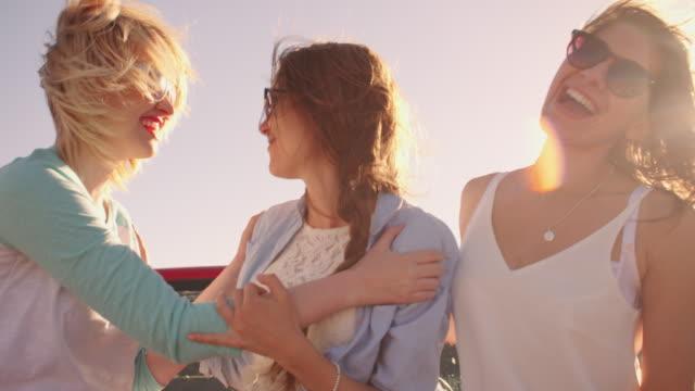 vidéos et rushes de femmes amis sur road trip en voiture décapotable tourné sur r3d - voiture blanche