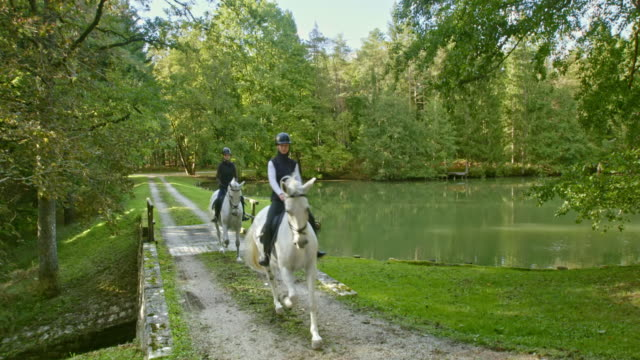 CS Female friends riding white horses across a lake bridge