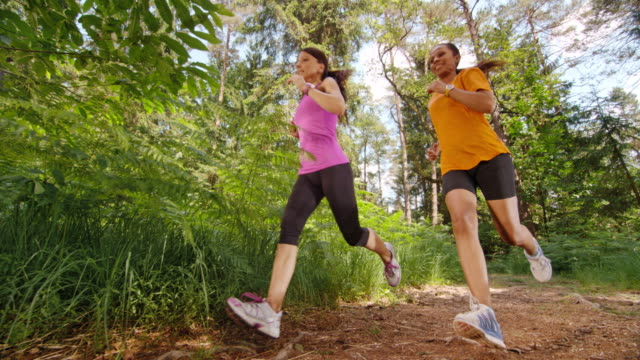 vidéos et rushes de slo, dans le missouri, cs femme amis courir dans la forêt - 40 44 ans