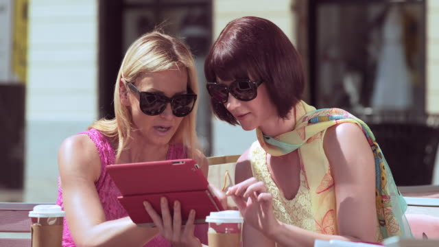 Female friends sitting outside while chatting and looking at tablet video
