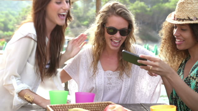 Female Friends Taking Selfie During Lunch Outdoors Group of female friends eating food at outdoor table and taking selfie on mobile phone.Shot on Sony FS700 at a frame rate of 25fps group of objects stock videos & royalty-free footage