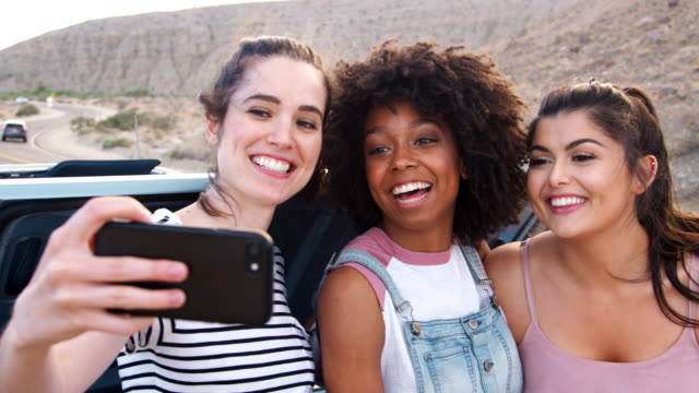 Female friends taking selfies during a break on road trip