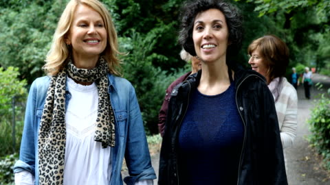 vídeos de stock e filmes b-roll de female friends talking while hiking in woodland - adulto maduro