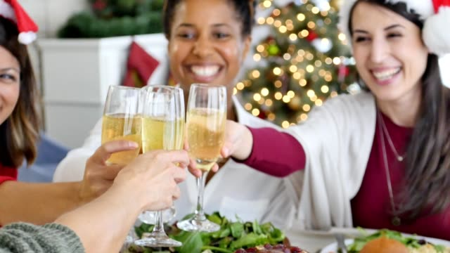 Female friends toast champagne during Christmas dinner video