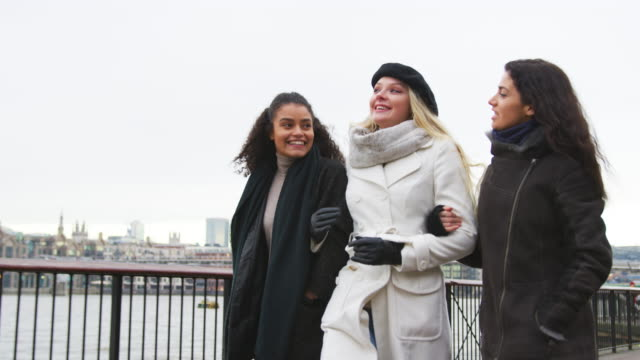 Female Friends Walk Along South Bank On Winter Visit To London video