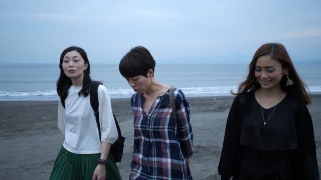 vidéos et rushes de amis féminins marchant sur la plage à l'heure de coucher du soleil - seulement des japonais