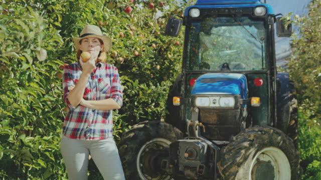 vídeos de stock e filmes b-roll de ds female fruit farmer eating an apple in apple orchard - agricultora
