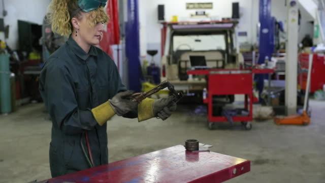 vídeos de stock, filmes e b-roll de trabalhador de garagem feminino vestindo macacão iluminação a gás, tocha de soldagem - soldar